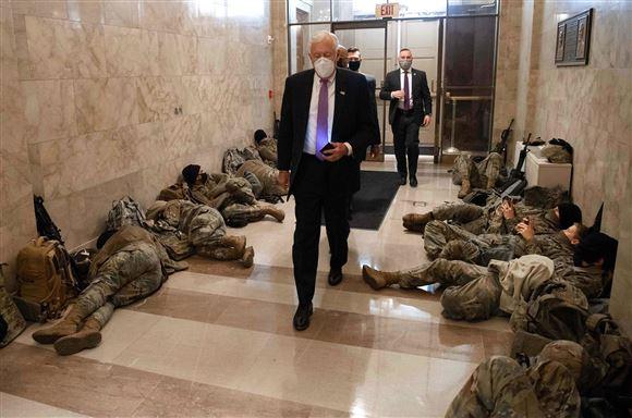 Kontorfolk går forbi sovende soldater