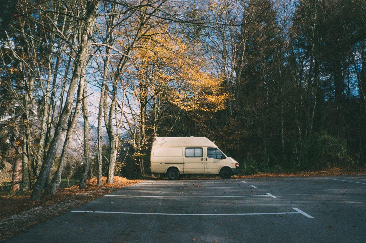 En gammel hvid varevogn parkeret alene på en parkeringsplads med visne træer omkring.