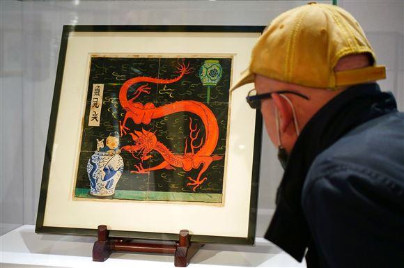 En mand set bagfra står og kigger på tegningen der er bag en glasmontre