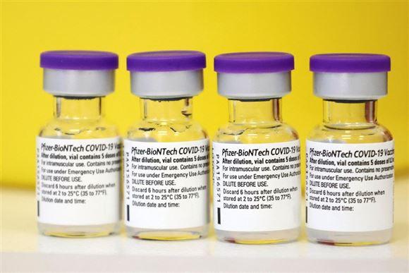 fire glas med coronavaccine på bord med gul baggrund
