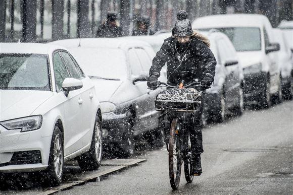 Mand kører på cykel i frostvejr