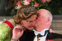 Kong Harlad giver dronning Sonja et kindkys. Hun har armen om ham.