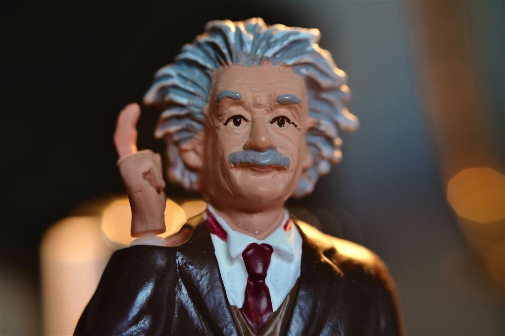 En dukke af Albert Einstein der rækker en finger i vejret.