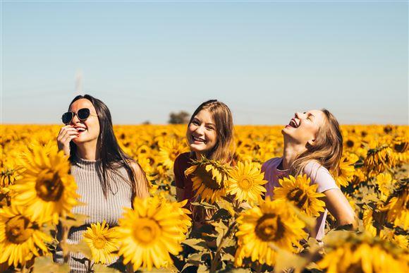 tre smilende piger på blomstermark