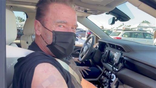 Arnold Schwarzenegger sidder i bil med sort mundbind og plaster på skulderen