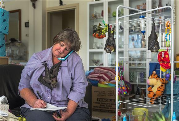 kvinde taler i telefon med en flyvende hund siddende på maven