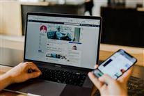 En computerskærm slået op på facebook og en hånd med en tændt smartphone i.
