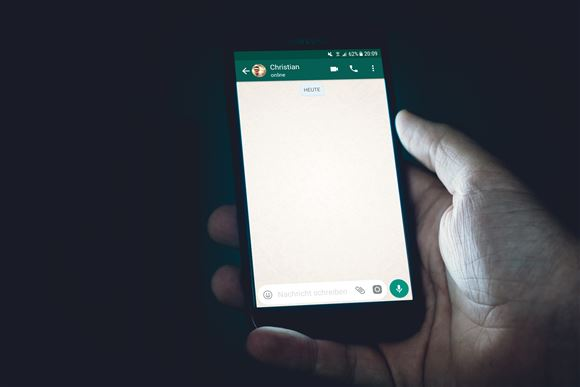 En smartphone i en hånd. Skærmen lyser klart op.