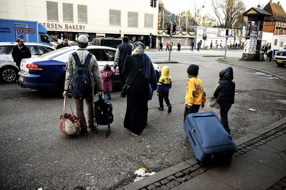 En familie med store kufferter går på en gade.