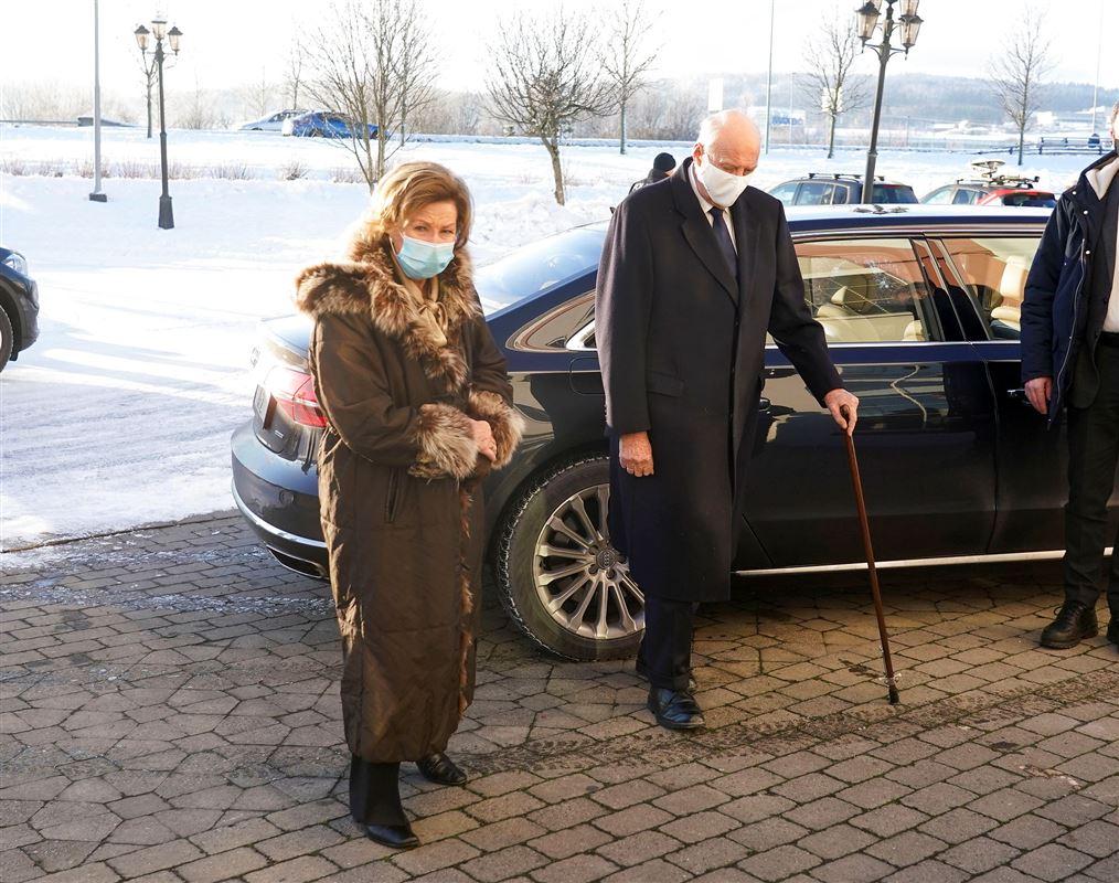 Kong harald og hans kone Sonja med mundben på efter de er steget ud af en bil. Kongen bruger stok på billedet.