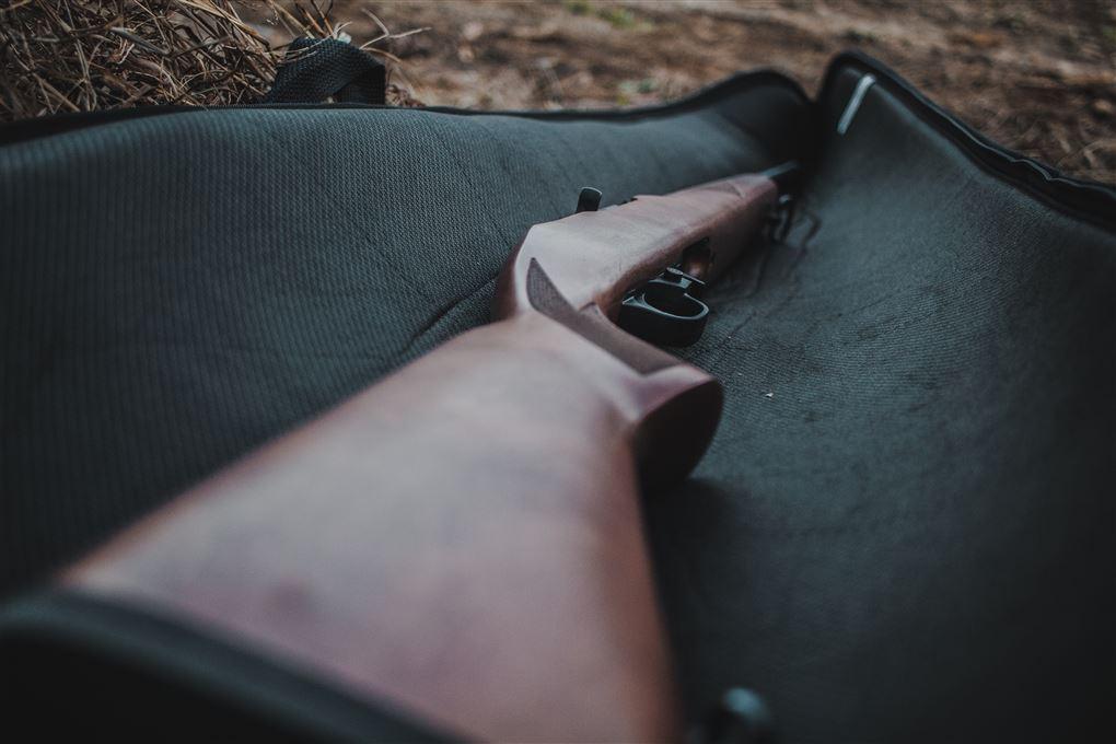 En riffel ligger på et hylster