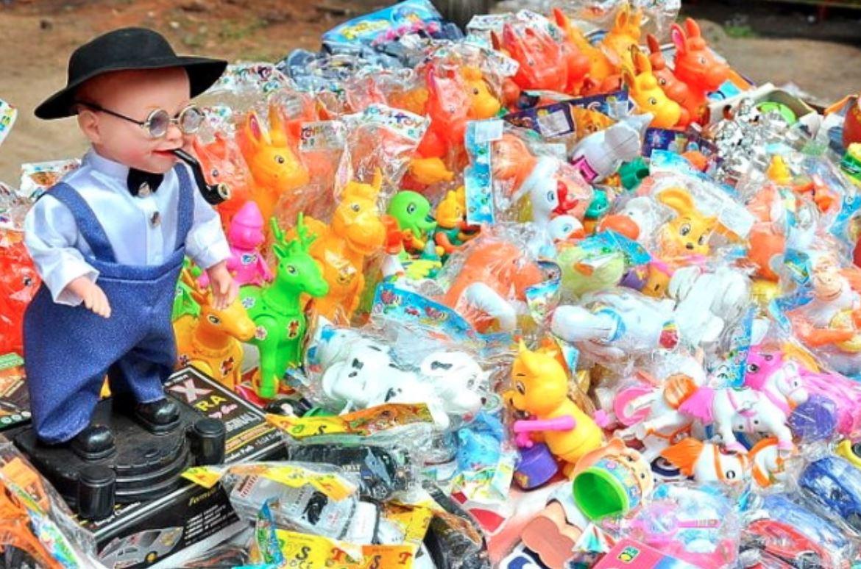 En plasticdukke af en lille dreng med pibe og en masse plastikdyr ved siden af