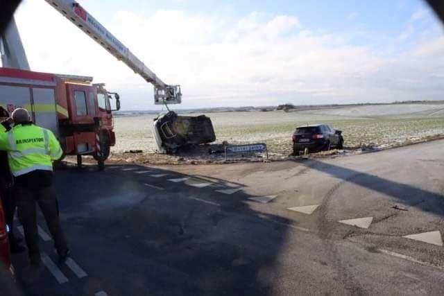 varevogn og bil ligger på mark efter trafikulykke