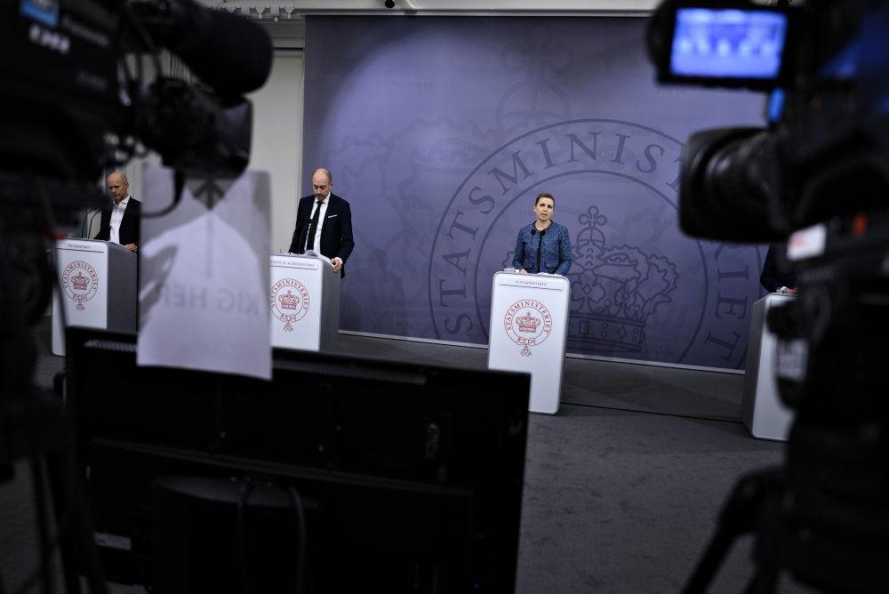 mette frederiksen og andre står på talerstole ved pressemøde