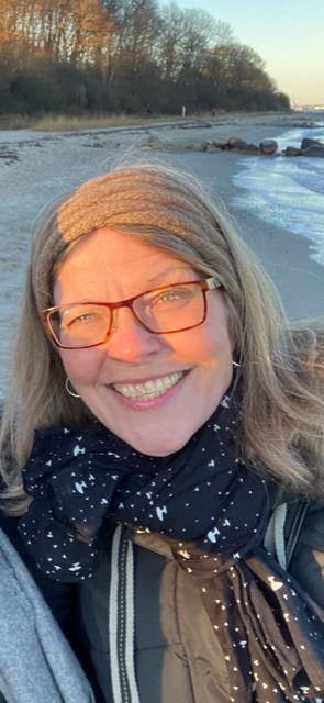 kvinde med røde briller smiler