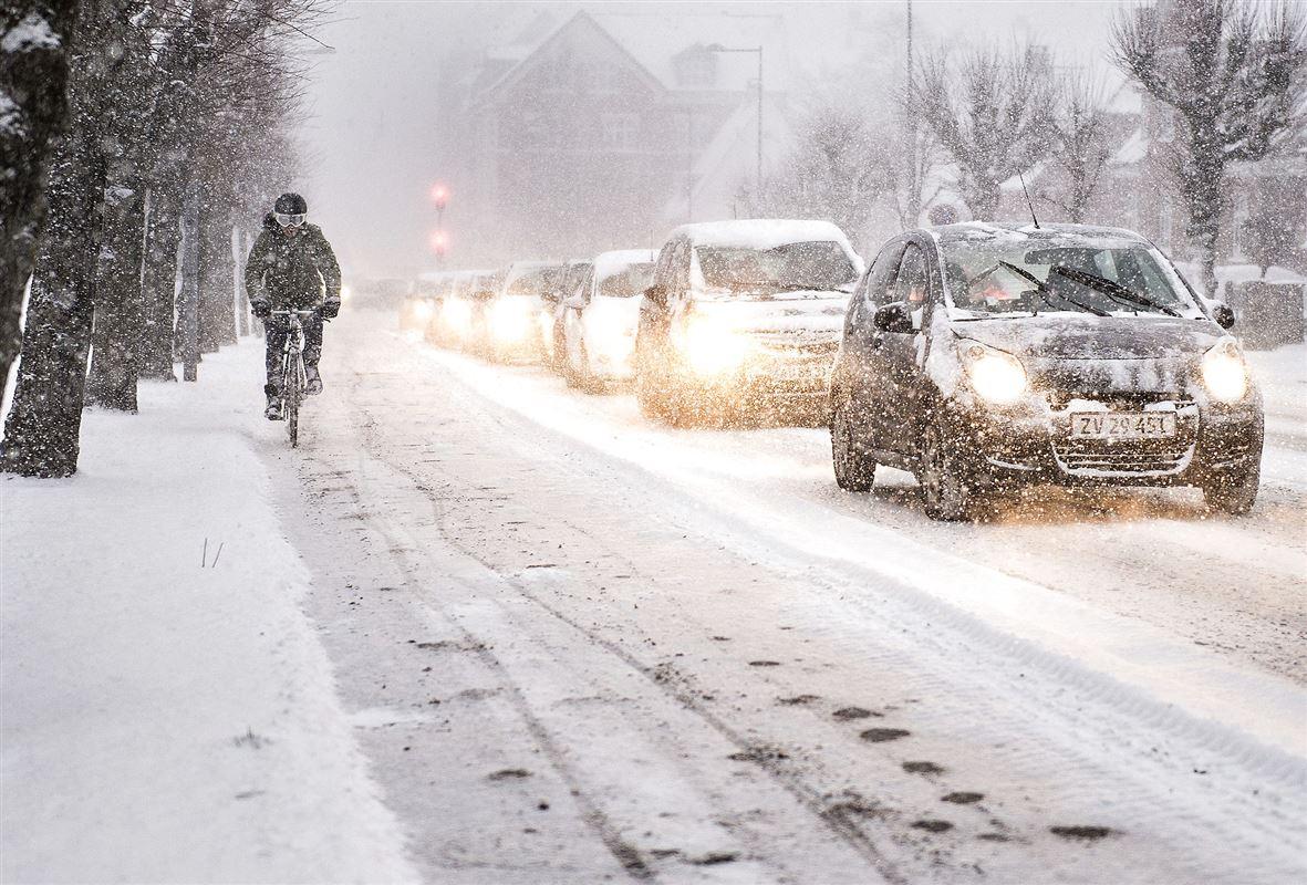 biler og cyklist kører i snevejr