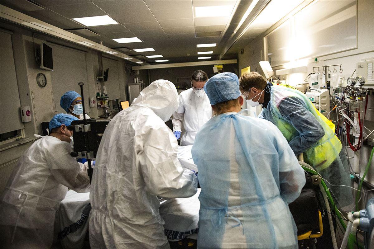 sundhedspersonale står tæt omkring seng på sygehus