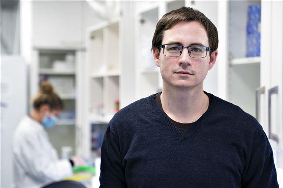 mand med briller står i laboratorie
