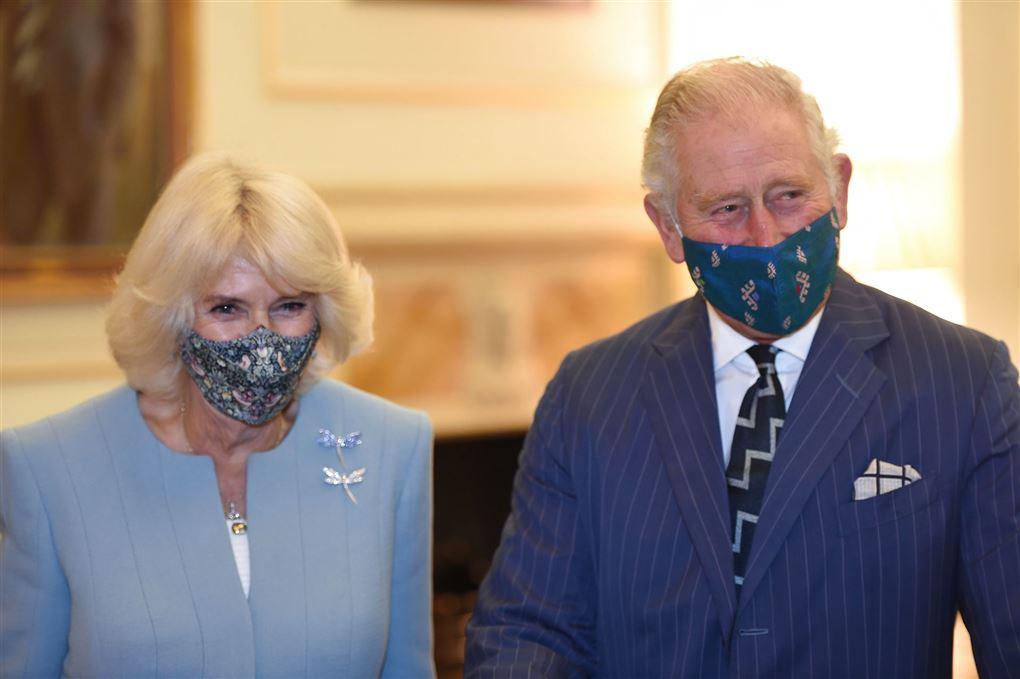 Camilla Parker Bowles og Prins Charles står med mundbind på