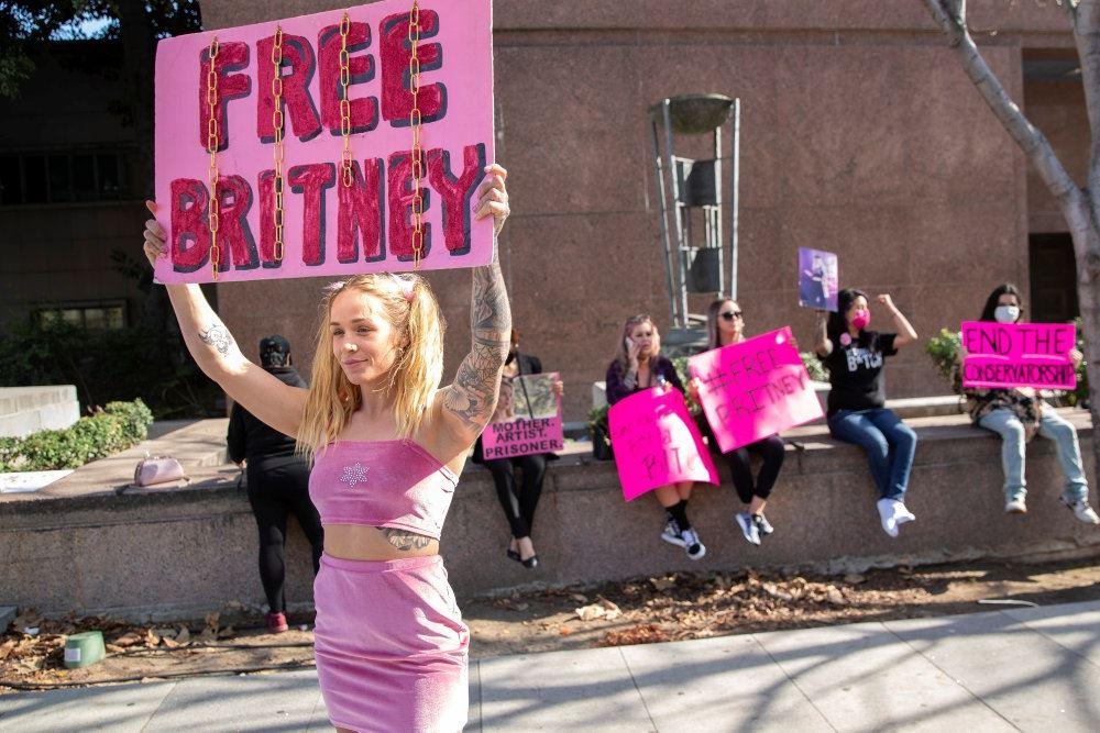 Britney-look-a-like med et Free Britney-skilt på gaden