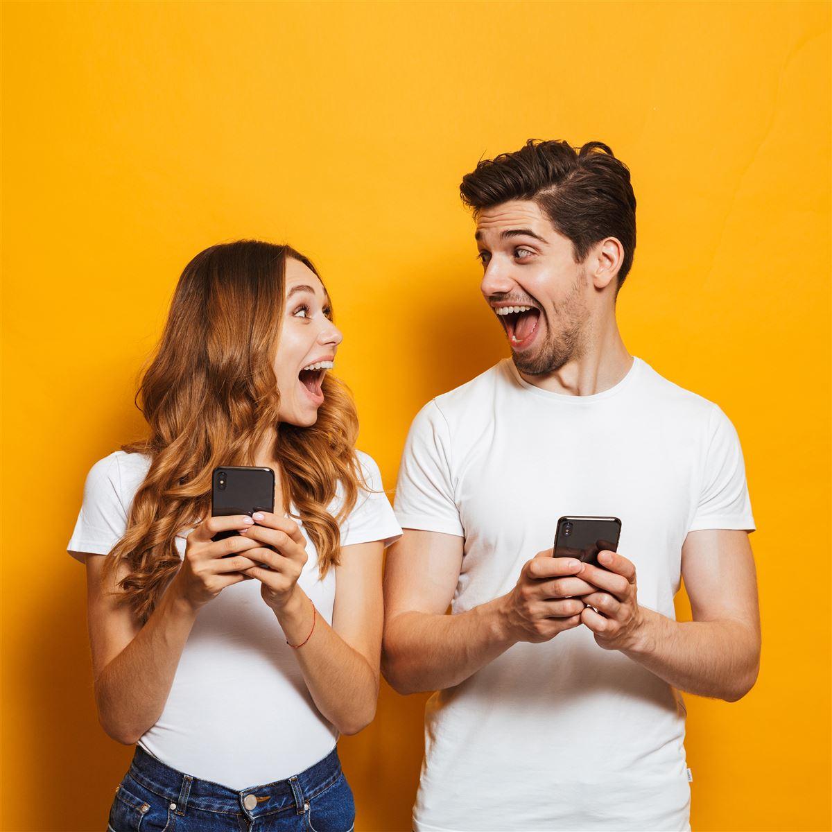 En mand og en kvinde holder hver sin mobiltelefon og ser meget begejstrede ud