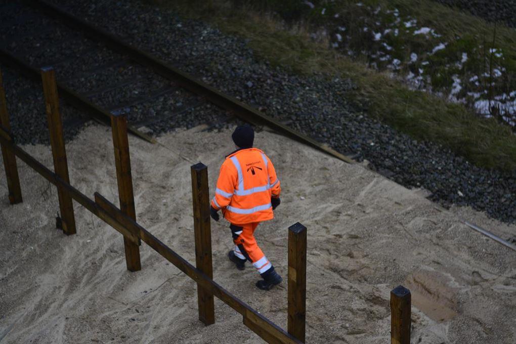 En DSB mand med orange vest på sandbunke