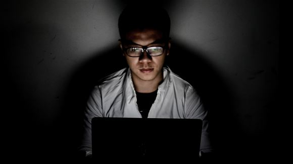 man sidder ved computer