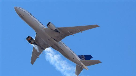 flyet ses i luften med røg fra den ene motor