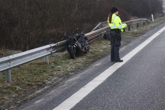 betjent står ved den smadrede motorcykel