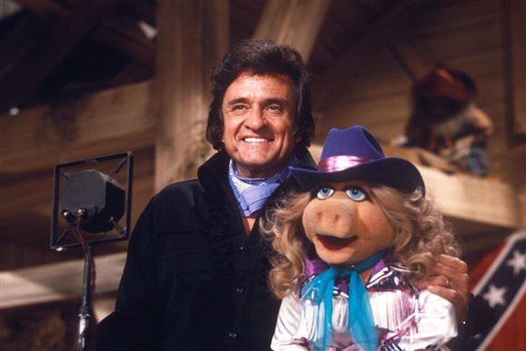 en smilende johnny cash i selskab med Miss Piggy i muppet show