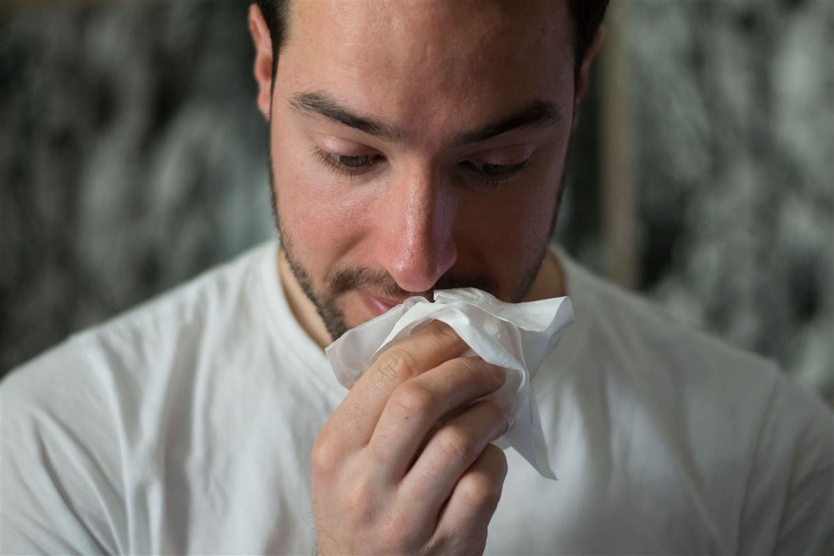 mand holder lommetørklæde op til næsen