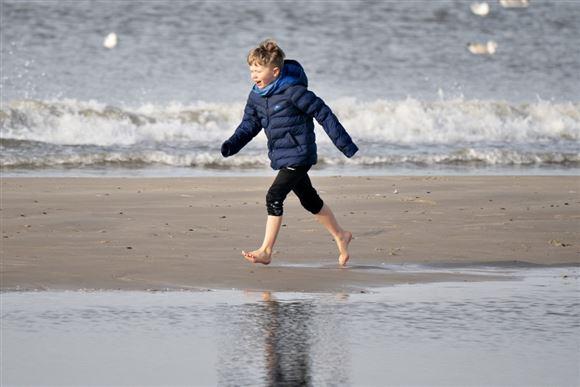 dreng løber på strand i bare tæer