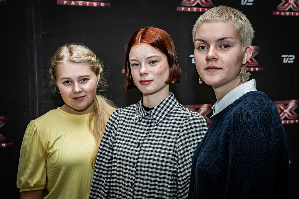 tre deltagere i x factor poserer for kameraet