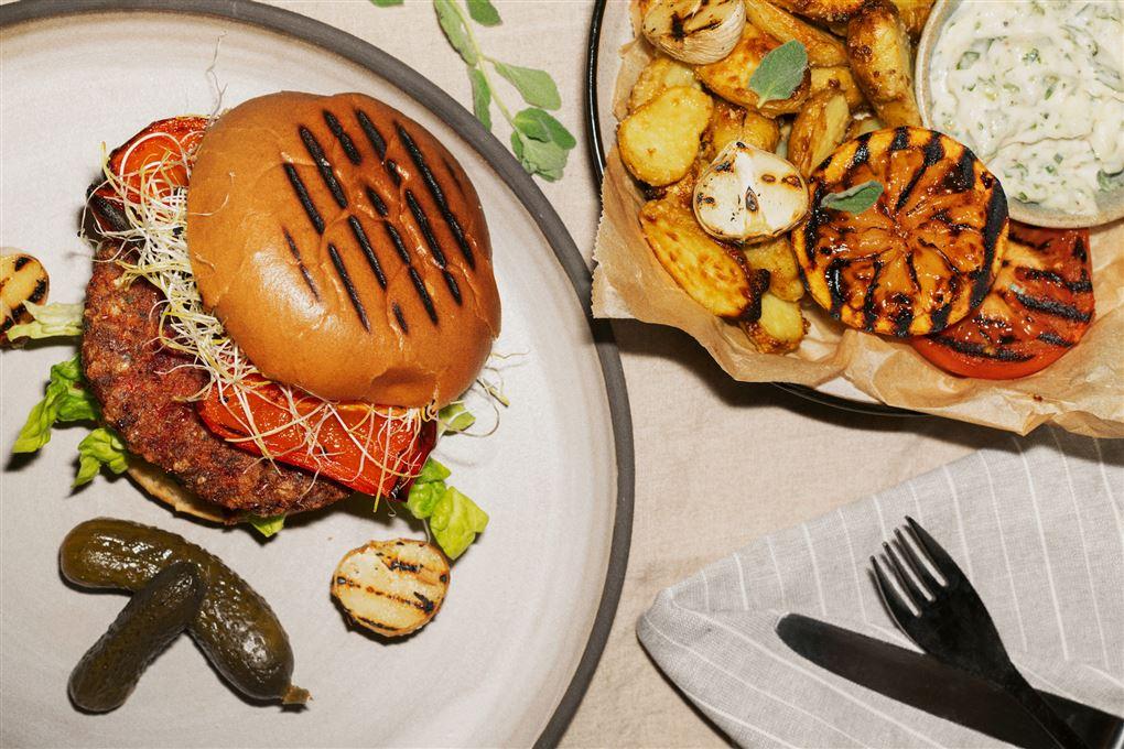 En burger på en tallerken med grønt