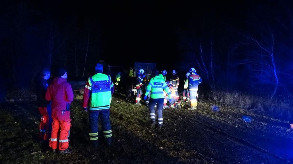 En masse redningsfolk både ambulance og brandmænd i mørket lyst op af blåt udrykningslys.