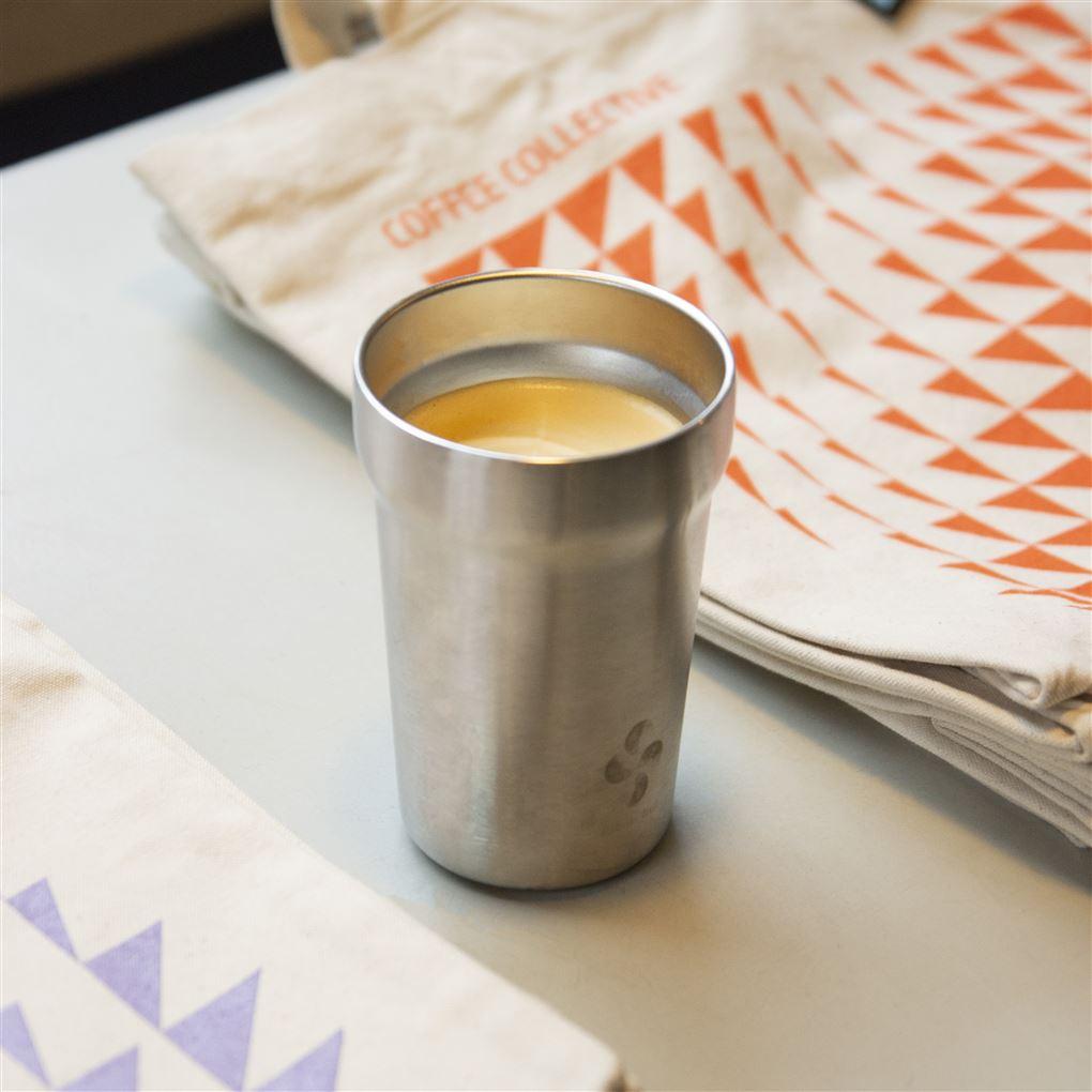 En rustfri kop med kaffe i på et bord