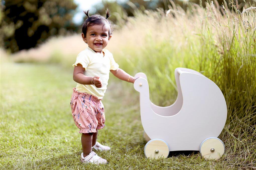 En lille pige med en dukkevogn