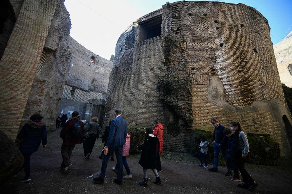 En ruinagtig bygning med menensker foran i Rom