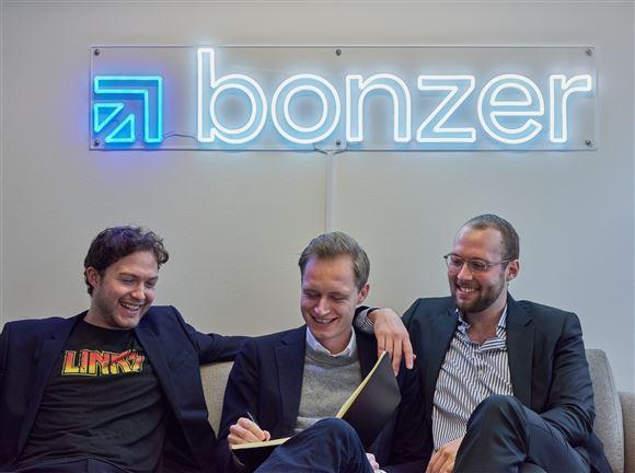 Tre mænd i en sofa med logo i neon bagved