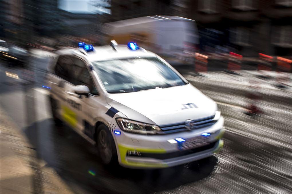 En politibil med udrykning kører på en vej.