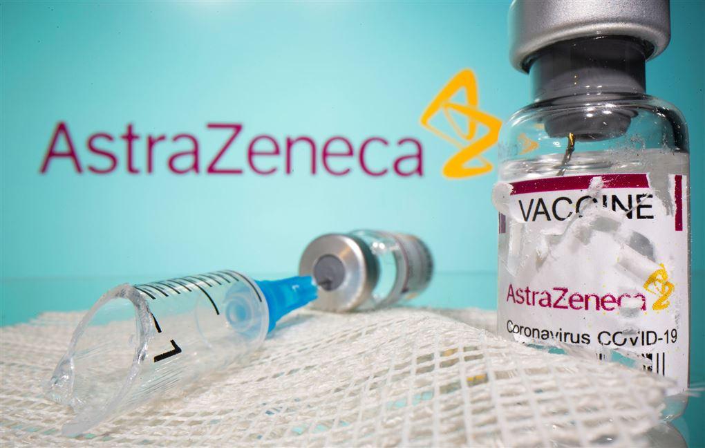 vaccineglas og kanyler på bord foran astra-zeneca-logo