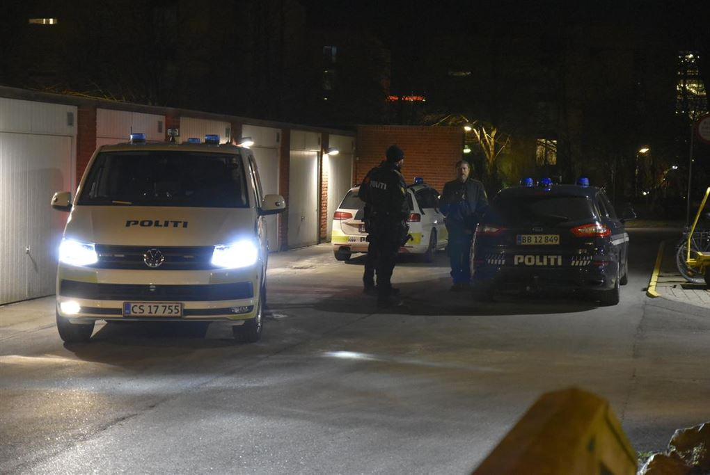 Politibiler og politifolk ved en garage