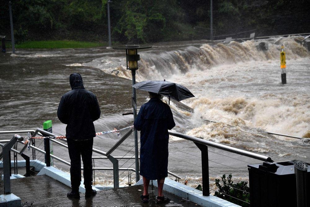 Lokale ser på, mens Parramatta-floden i Sydney går over sine bredder . Vejen er fyldt med vand.