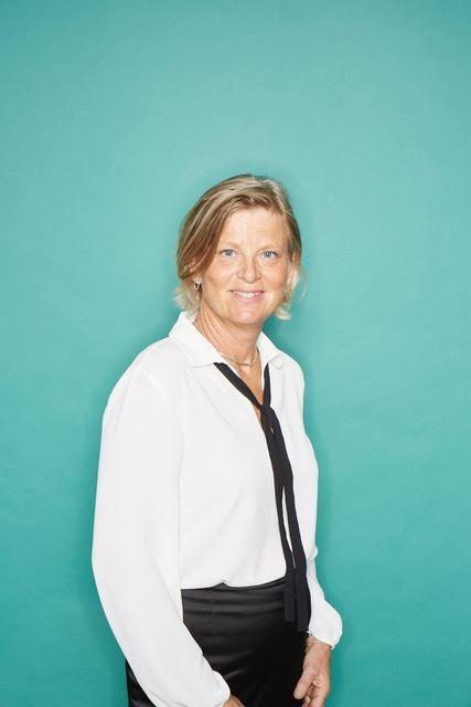 En smilende dame med hvid skjorte og slips