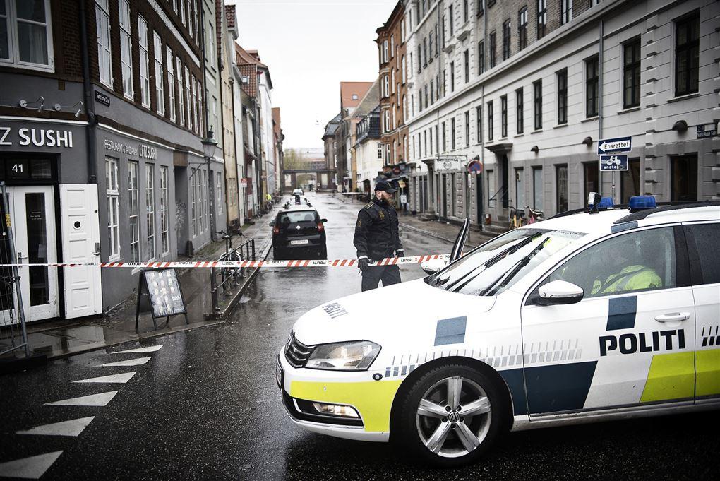 politibil holder på gade med afspærringsbånd