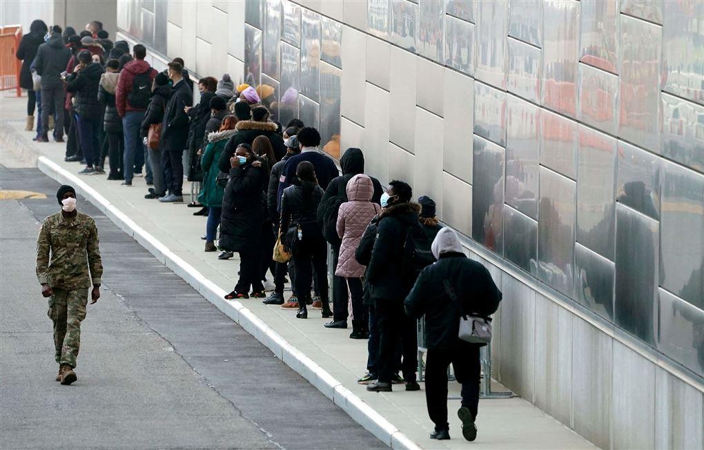 folk står i kø på gaden