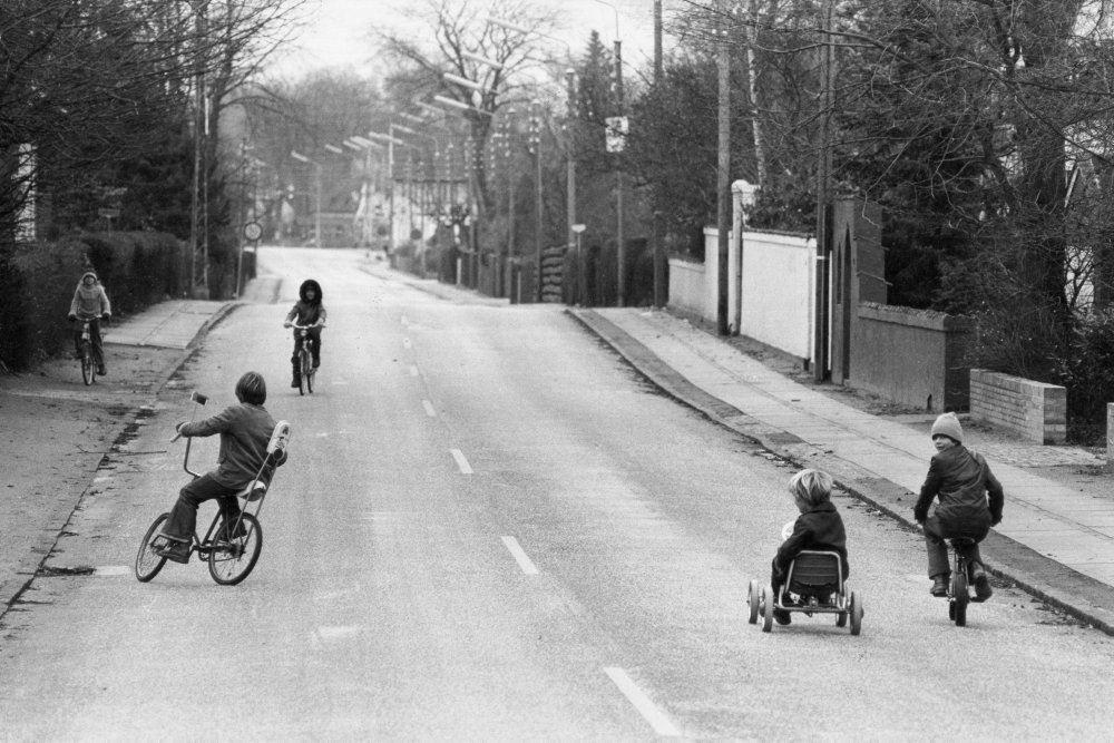 et sort hvidt foto af en tom vej med legende børn på