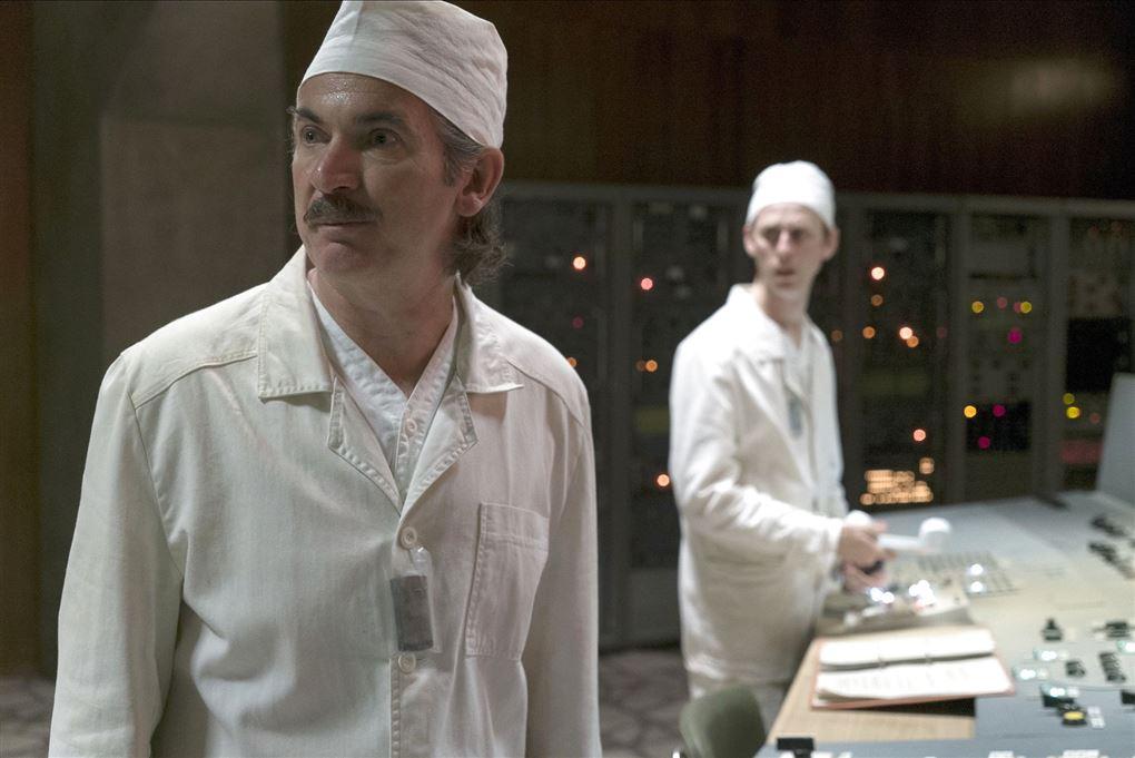 to hvidklædte mænd står i kontrolrum