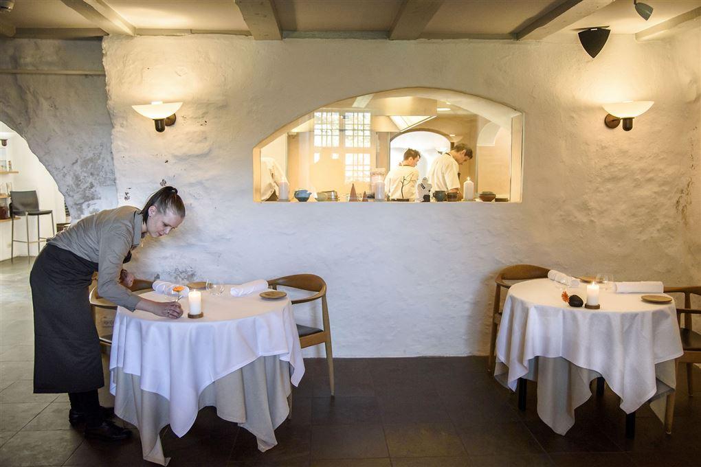 """En kvindelig tjener læner sig ind over et bord med en hvid dug og retter på et stearinlys, Bag hende ses to kokke igennem et """"hul"""" i væggen fra restaurant til køkken."""