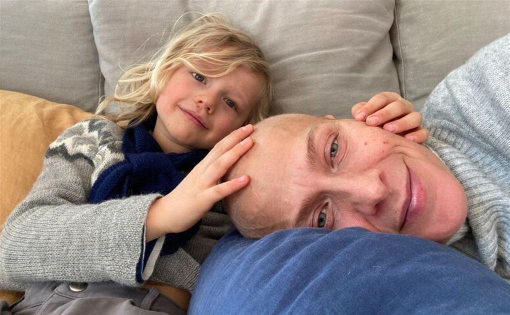 En skaldet mor med en lille dreng på sofaen.